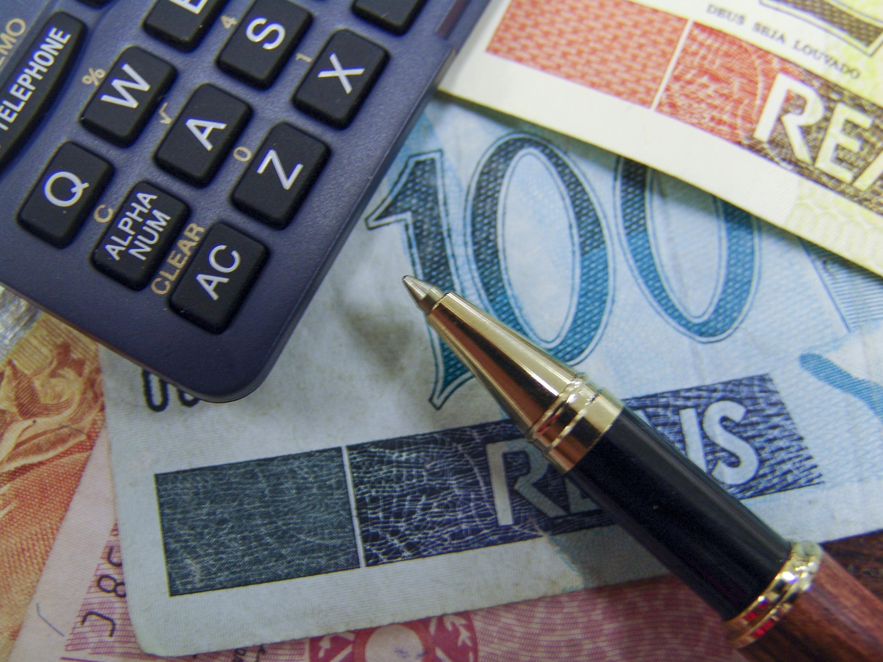 Mixed brazilian money notes, pen and calculator.